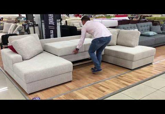 парень раскладывает диван
