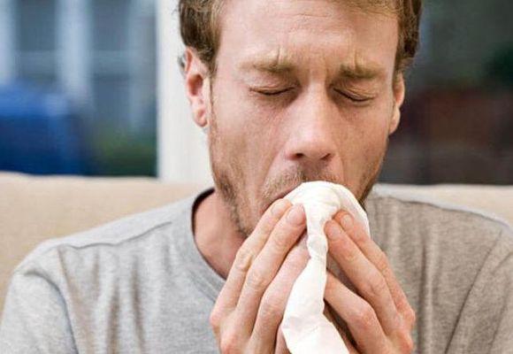 мужчина зевает с платком у рта