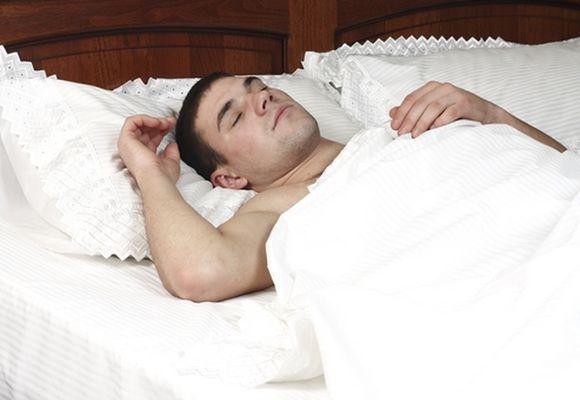 мужчина спит на подушке под одеялом