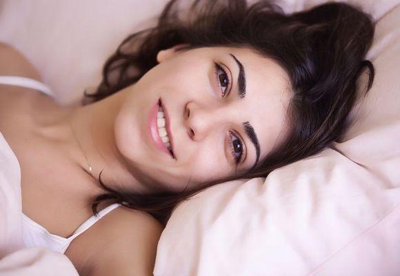 девушка улыбается на подушке