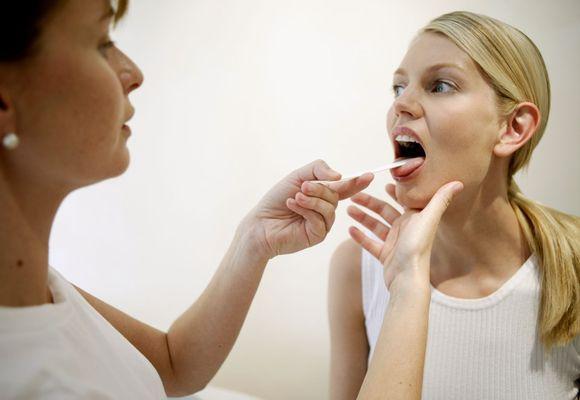 девушке проверяет горло врач