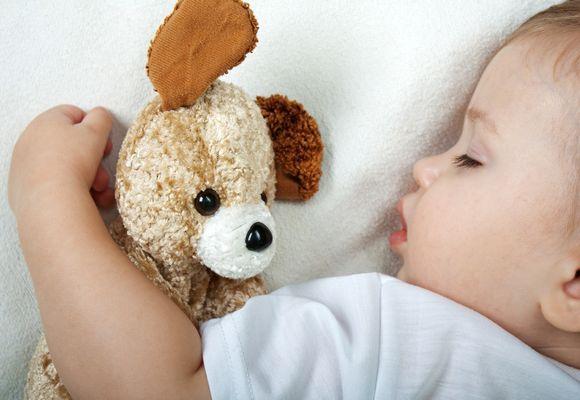 ребенок спит с игрушкой в руке