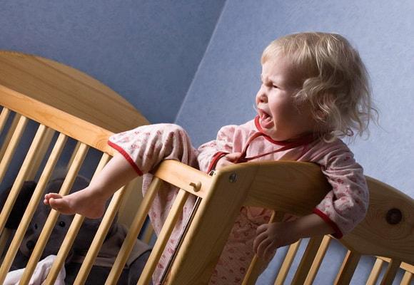 ребенок в кроватке плачет
