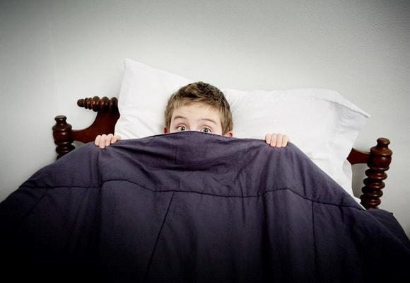 ребенок прячется под одеяло