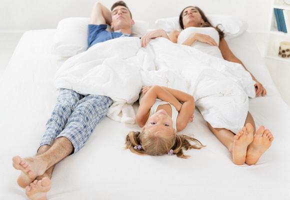 Девочка в кровати с родителями