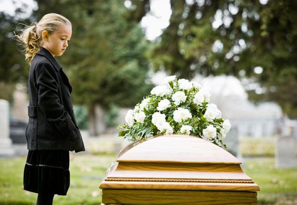 Девочка стоит рядом с гробом
