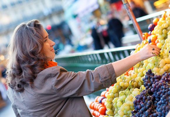 Женщина покупает виноград на рынке