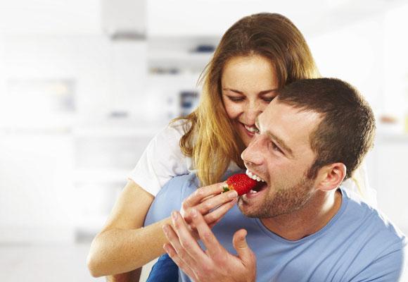 Девушка кормит клубникой мужчину