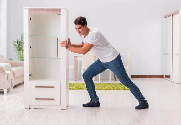 Мужчина двигает шкаф