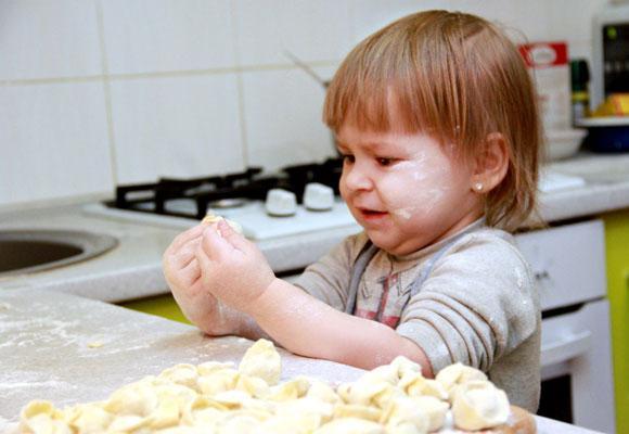 Ребенок лепит пельмени